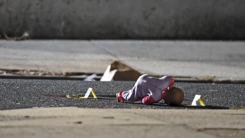 In this Monday, Nov. 19, 2018, photo, a child's doll lays next to police shooting evidence tags, as