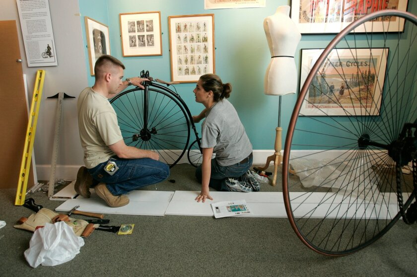 Emily Allen, director of exhibits at the Coronado Historical Society, secured a vintage 1885 Rudge Racer to a stand with the help of her husband, Aaron.