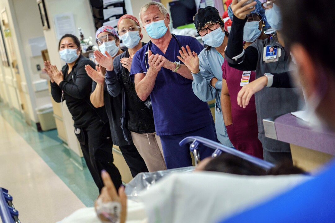 Healthcare workers celebrate as a patient is discharged from the ICU.