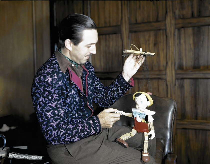 "Walt Disney, shown here examining a Pinocchio marionette circa 1939, is the subject of an ""American Experience"" documentary on PBS."