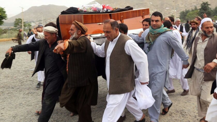 Mourners carry the coffin June 3 of one of the people killed during a violent protest in Kabul, Afgh