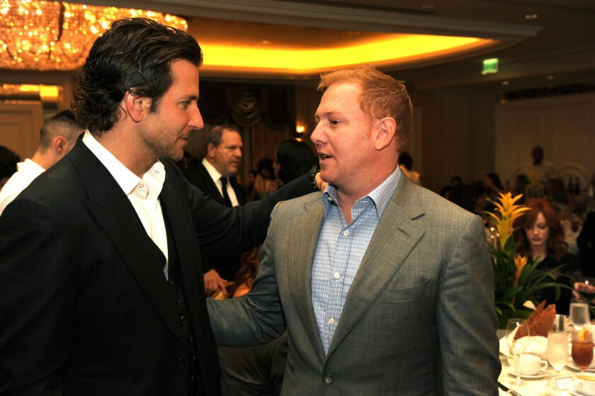 Ryan Kavanaugh, pictured here with Bradley Cooper in 2012, is unable to make payments on $320 million in debt and has started layoffs at Relativity Media.