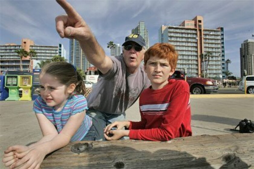 Jeff Leavitt of La Mesa brought his grandchildren Delaney (left) and Camden to the Embarcadero yesterday afternoon in the hope of spotting the gray whale in San Diego Bay. (John Gibbins / Union-Tribune)
