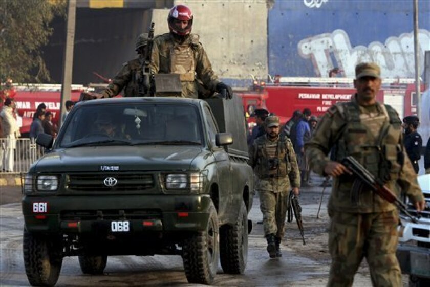Pakistan's army soldier stand guard near the site of a burning oil tanker, carrying fuel supplies for NATO forces in neighboring Afghanistan, after it was allegedly attacked by militants in Peshawar, Pakistan, Monday, Feb. 1, 2010. Militants have frequently attacked trucks traveling through the Khyber pass carrying supplies to NATO and US troops in landlocked Afghanistan. (AP Photo/Mohammad Sajjad)