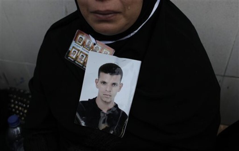 In this Friday, July 8, 2011 photo, the mother of slain Mohammed Yousef, who was killed during the Egyptian revolution, reacts with a picture of her late son around her neck while taking part in a demonstration in Suez, Egypt. (AP Photo/Nasser Nasser)