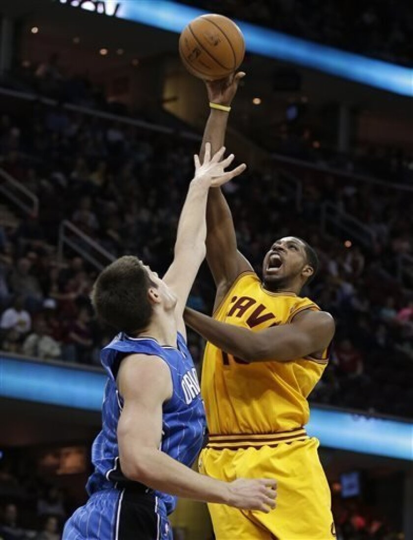 Cleveland Cavaliers' Tristan Thompson (13) shoots over Orlando Magic's Nikola Vucevic (9), from Montenegro, during the second quarter of an NBA basketball game Sunday, April 7, 2013, in Cleveland. (AP Photo/Tony Dejak)