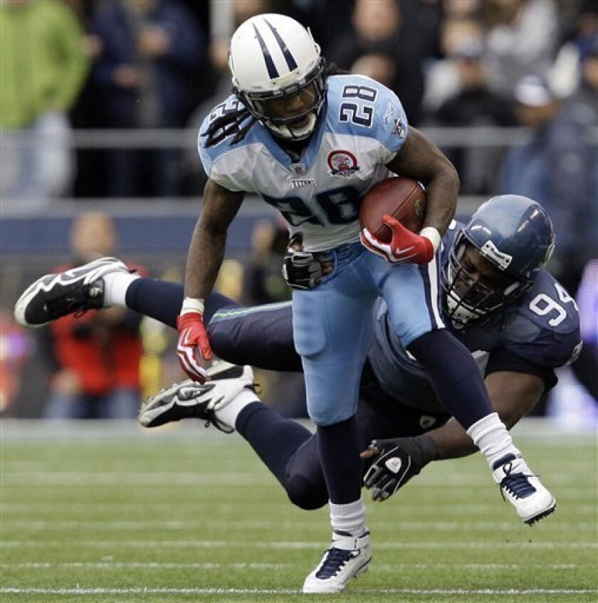 Tennessee Titans Chris Johnson (28) runs with the ball as Seattle Seahawks' Cory Redding attempts the tackle in the first half on Sunday, Jan. 3, 2010, during an NFL football game in Seattle. (AP Photo/Elaine Thompson)