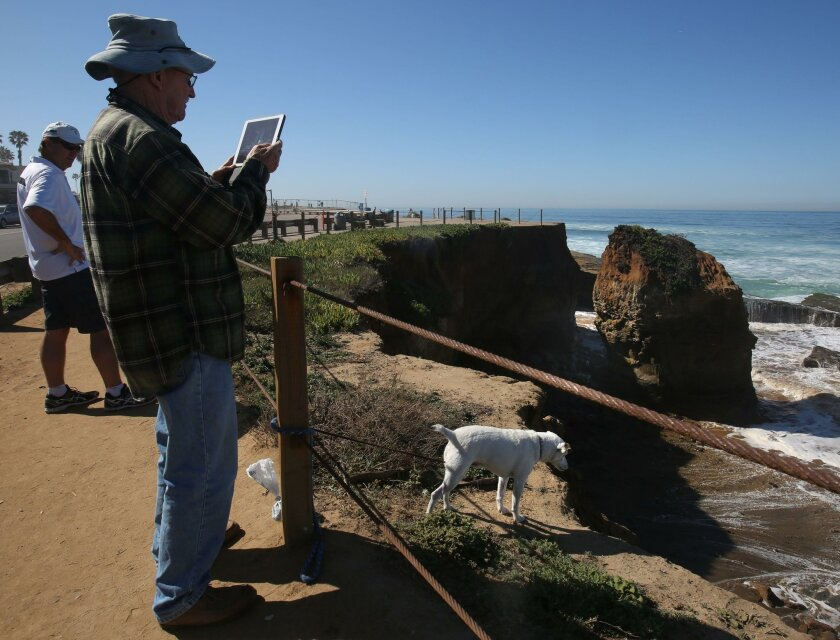 Ocean Beach resident Allen Pollock takes photos of the new cliff collapse scen along Sunset Cliffs Thursday as his dog Larry sniffs close to the edge. A section of Sunset Cliffs collapsed in the early morning hours Thursday. What used to be an arch from the parking lot over to a tall rocky pillar is now gone and a large gap separates the two. The parking lot on Sunset Cliffs Blvd. between Adair and Osprey Streets had already been closed off by city workers with a cyclone fence back in late January due to cracks developing in the asphalt and the arch below eroding noticeably.