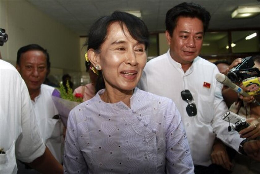 Myanmar pro-democracy icon Aung San Suu Kyi smiles as she talks to journalists upon her arrival back at Yangon airport from Naypyitaw Wednesday, April 11, 2012, in Yangon, Myanmar. The architects of political reconciliation in Myanmar, President Thein Sein and opposition leader Suu Kyi, met Wednesday ahead of the Nobel peace laureate's historic entry into parliament. (AP Photo/Khin Maung Win)