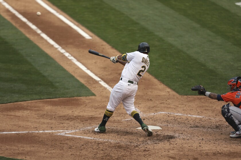 Oakland Athletics' Khris Davis hits an RBI double against the Houston Astros during the sixth inning of the first baseball game of a doubleheader in Oakland, Calif., Tuesday, Sept. 8, 2020. (AP Photo/Jed Jacobsohn)