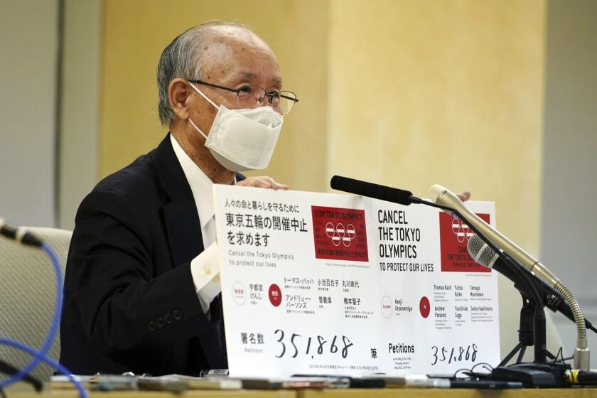 "A man holds a ""Cancel the Tokyo Olympics"" placard."