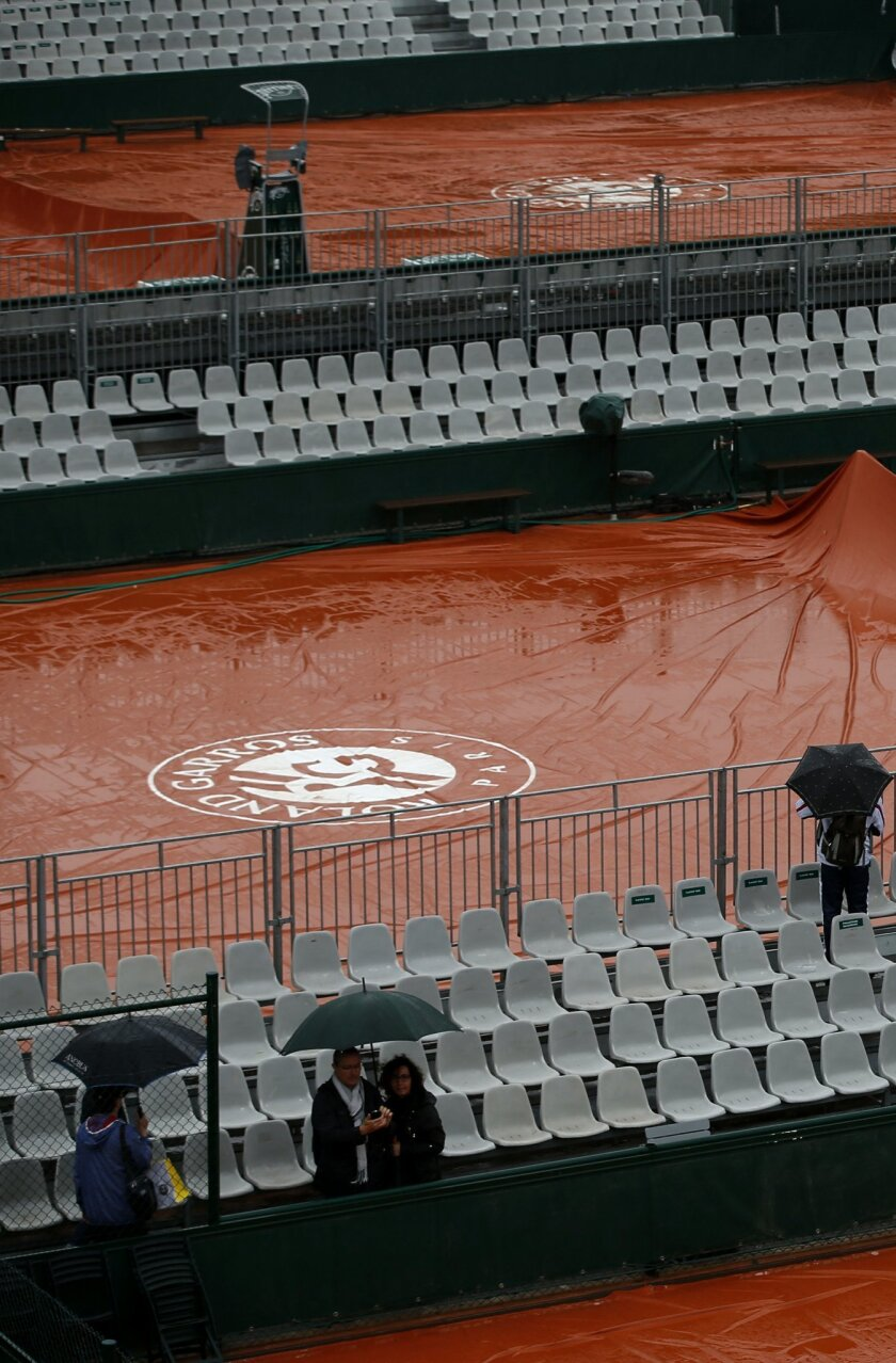 Rain cover protect courts at the Roland Garros stadium, Monday, May 30, 2016 in Paris. French Open organizers have announced the cancellation of all matches Monday at Roland Garros because of persistent rain forecast to last all day. (AP Photo/Alastair Grant)