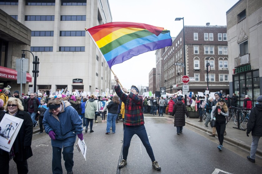 Jamie Killips of Madison waves an LGBT pride flag Saturday, Jan. 21, 2017, during the Women's March near State Street in Madison, Wis.