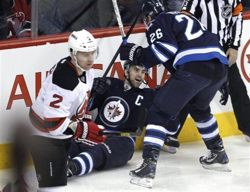 Winnipeg Jets' Andrew Ladd, center, celebrates his goal against the New Jersey Devils with teammate Blake Wheeler (26) during the first period of an NHL hockey game in Winnipeg, Manitoba, on Thursday, Feb. 28, 2013. (AP Photo/The Canadian Press, John Woods)