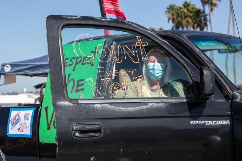 Susan Beattie prepares a vehicle for a caravan through downtown on Wednesday, Nov. 4, 2020 in San Diego, CA.