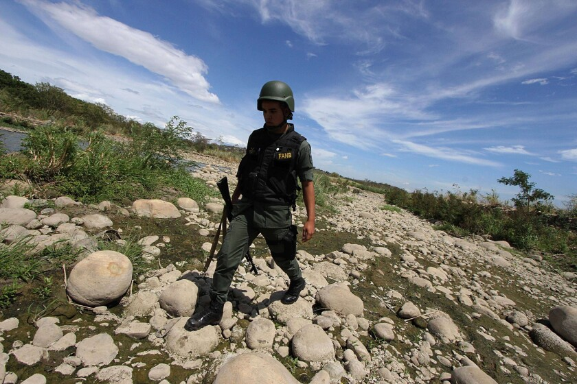 A member of the Venezuelan National Guard patrols along the Tachira River, which forms the border with Colombia, on Sept. 5, 2014. The low prices for gasoline and basic goods in Venezuela encourages the flow of scarce commodities into neighboring Colombia.