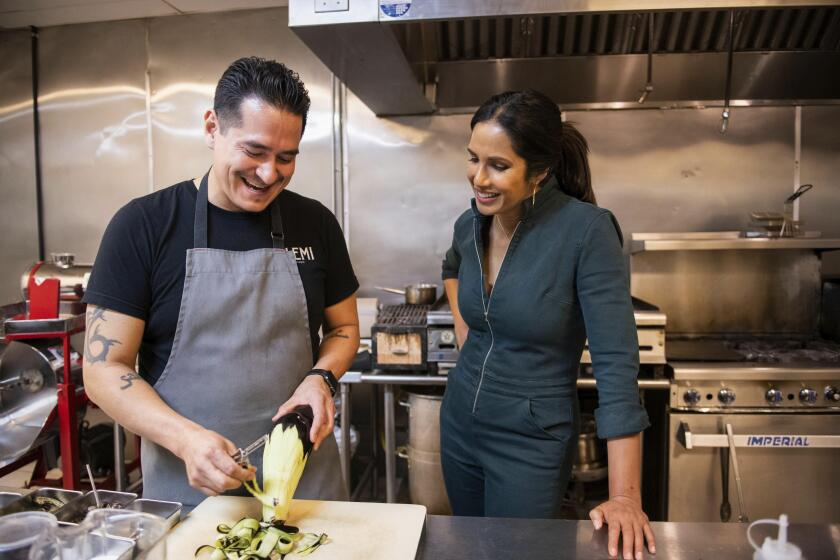 """In this image released by Hulu, Emiliano Marentes, left, owner of Elemi, appears in his kitchen as host Padma Lakshmi looks on, in a scene from """"Taste the Nation,"""" a documentary series streaming on Hulu. (Dominic Valente/Hulu via AP)"""