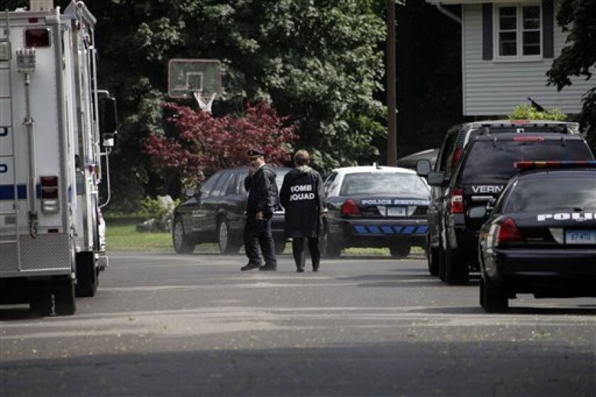 Police officers move down Tumblebrook Drive in South Windsor, Conn., Tuesday, July 7, 2009. A Connecticut advertising executive who police say is holding his ex-wife hostage has told a reporter he wants a priest brought in to give the woman her last rites. (AP Photo/Bob Child)