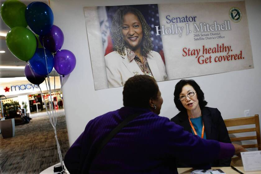 Certified counselor Helen Lee, right, signs up a woman for health coverage at a Covered California exchange office in the Baldwin Hills Crenshaw mall.