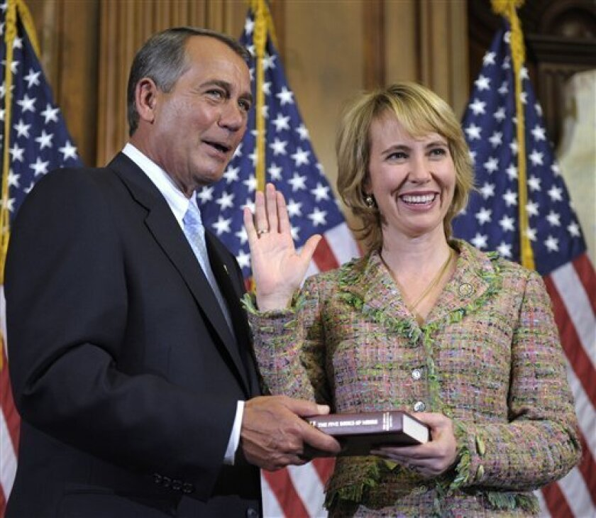 FILE - In this Jan. 5, 2011 file photo, House Speaker John Boehner reenacts the swearing in of Rep. Gabrielle Giffords, D-Ariz., on Capitol Hill in Washington. Authorities say that Giffords was shot in the head on Saturday, Jan. 8, 2011 while meeting with constituents in her district in the area around Tucson. (AP Photo/Susan Walsh, File)