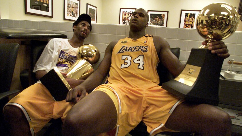 Lakers stars Kobe Bryant and Shaquille O'Neal hold the championship trophies after winning Game 6 of the 2000 NBA Finals.