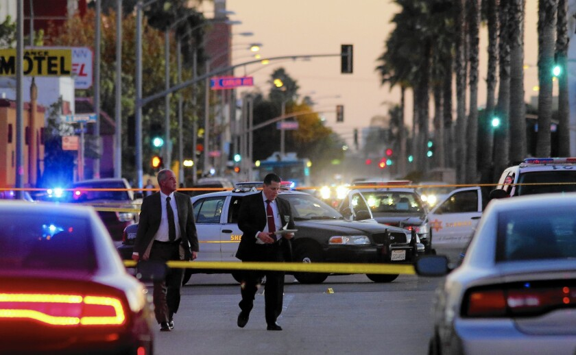 Law enforcement officials investigate the area where sheriff's deputies fatally shot a man outside a Lynwood gas station. The incident was recorded on video.
