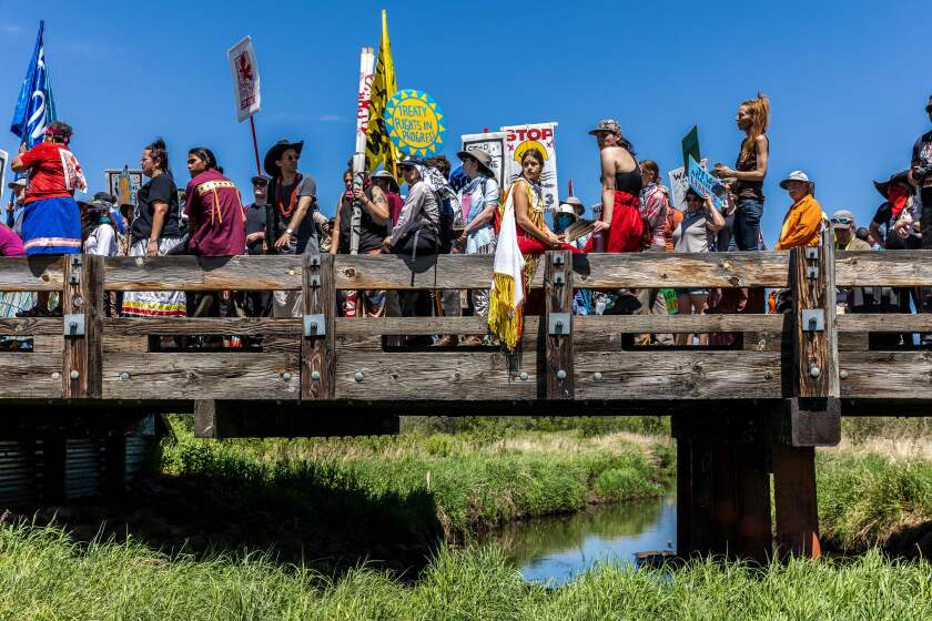 Climate activists and Indigenous community members on a bridge