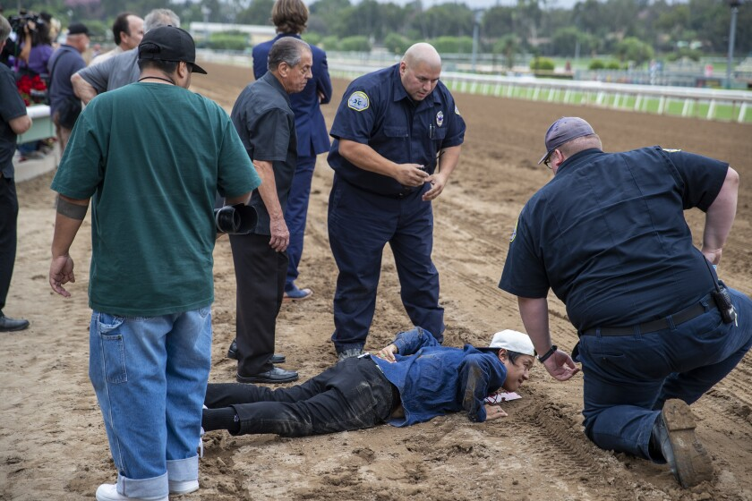 Santa Anita medics attend to an injured photographer after his back was run over by Leucothea on Friday.