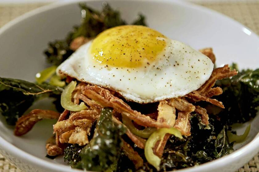 Fried pig ears and crispy kale are topped with a fried egg at the Purple Pig. Recipe