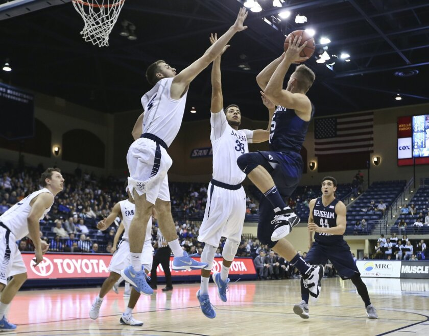 BYU guard Kyle Collinsworth looks for an escape pass as San Diego guard Vasa Pusica, left, and center Jito Kok defend during the first half of an NCAA college basketball game Thursday, Feb. 18, 2016, in San Diego. (AP Photo/Lenny Ignelzi)