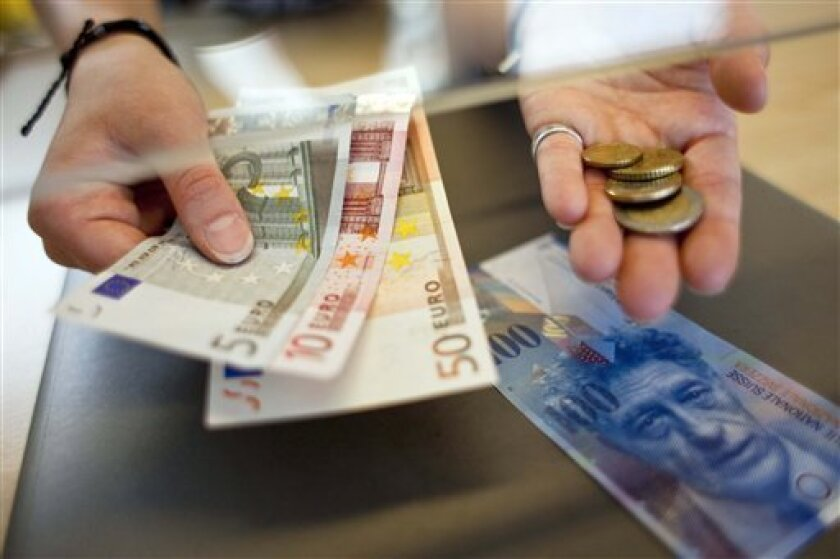 "FILE - The June 8, 2011 file photo shows a woman changing Swiss francs to Euro at a counter in Kreuzlingen, Switzerland. The Swiss National Bank set a ceiling on the value of the country's strong currency on Tuesday, using what experts called a last-ditch ""nuclear option"" to protect its economy and keep exporters competitive. The bank said it would spend whatever it takes to keep the currency from strengthening beyond 1.20 francs per euro and indicated it might take more measures to weaken it further. (AP Photo/Keystone, Ennio Leanza) GERMANY OUT AUSTRIA OUT"