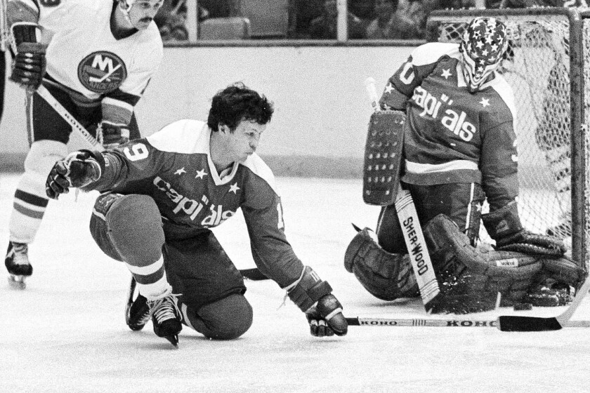 FILE - In this Feb. 4, 1978, file photo, Washington Capitals' Bryan Watson, left, helps to defend as goalie Bernie Wolfe make the save in the first period of an NHL hockey game agains the New York Islanders in Uniondale, N.Y. Watson, who played for Scotty Bowman, with Doug Harvey and coached Wayne Gretzky, has died. He was 78. Watson played 1,009 games in the NHL for Montreal, Detroit, Oakland, Pittsburgh, St. Louis and Washington from 1963-1978 before finishing his on-ice career with Cincinnati in the World Hockey Association in 1979. (AP Photo/Harry Harris, File)