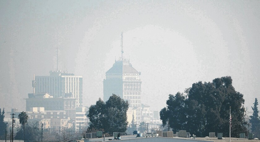The downtown Fresno skyline, cloaked in thick haze, on Jan. 17. The amount of fine particles known as PM-2.5 in the air is now so high that even otherwise healthy adults are at risk.