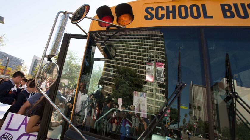 Students board a bus back to school after walking out of class and attending a march in downtown Los Angeles on Nov. 14, 2016.