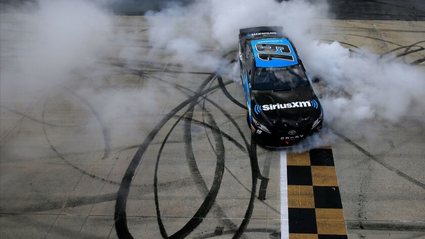 Martin Truex Jr. celebrates with a burnout after winning a NASCAR race at Dover International Speedway on May 6.