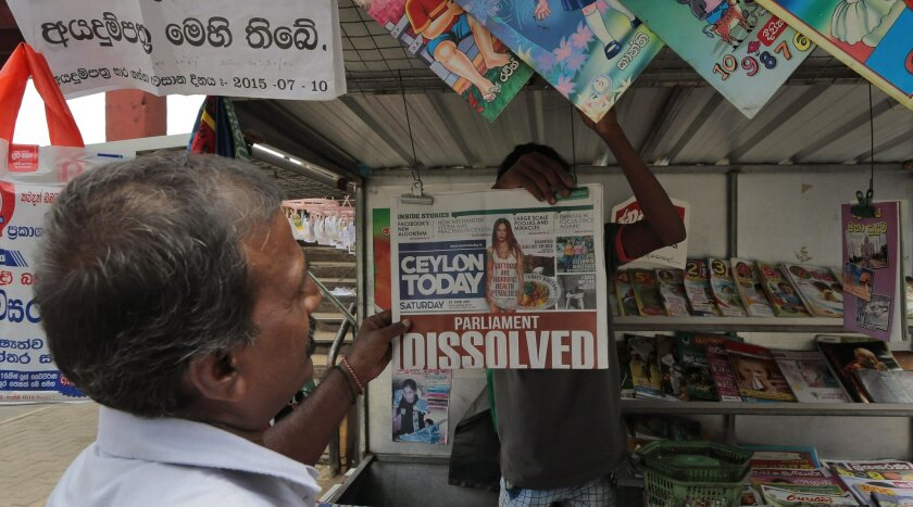 A Sri Lankan man looks at a newspaper at a stall in Colombo, Sri Lanka, Saturday, June 27, 2015. Sri Lanka's President Maithripala Sirisena dissolved Parliament loyal to his predecessor and called fresh elections in August in an attempt to consolidate power and carry out his promise of reforms. (AP
