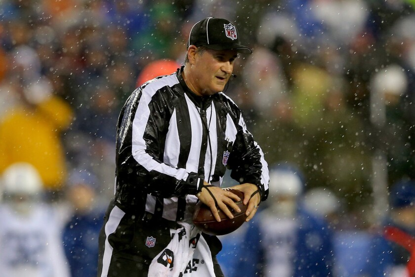 Umpire Carl Paganelli holds a football during the AFC Championship game between the New England Patriots and Indianapolis Colts. The Patriots beat the Colts, 45-7.