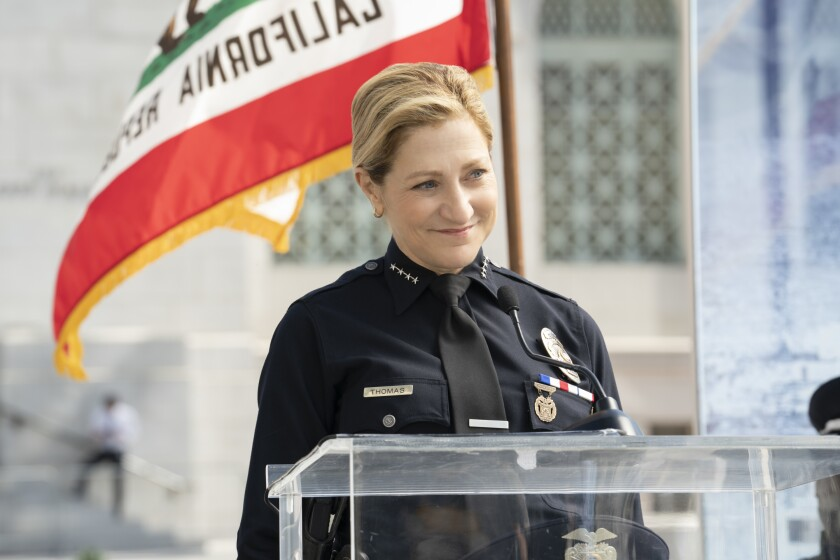 """Edie Falco, wearing a police uniform, stands at a clear lectern with the California flag waving behind her in """"Tommy."""""""