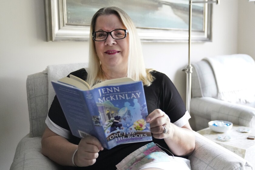 Kelly Vaiman poses for a photo in her living room where she sometimes likes to sit and read, Friday, Feb. 19, 2021, in Boynton Beach, Fla. Vaiman is an avid cozy mystery reader. (AP Photo/Wilfredo Lee)