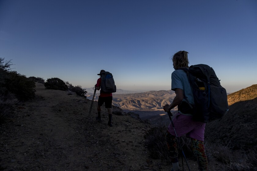 Hikers with backpacks overlooking mountains