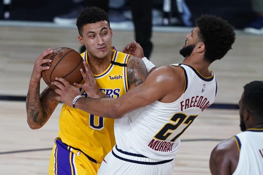 Lakers' Kyle Kuzma drives to the basket against Denver Nuggets' Jamal Murray.