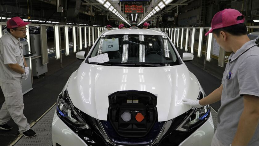 Chinese workers inspect a Nissan Sylphy Zero Emission, Nissan's first all-electric vehicle built in