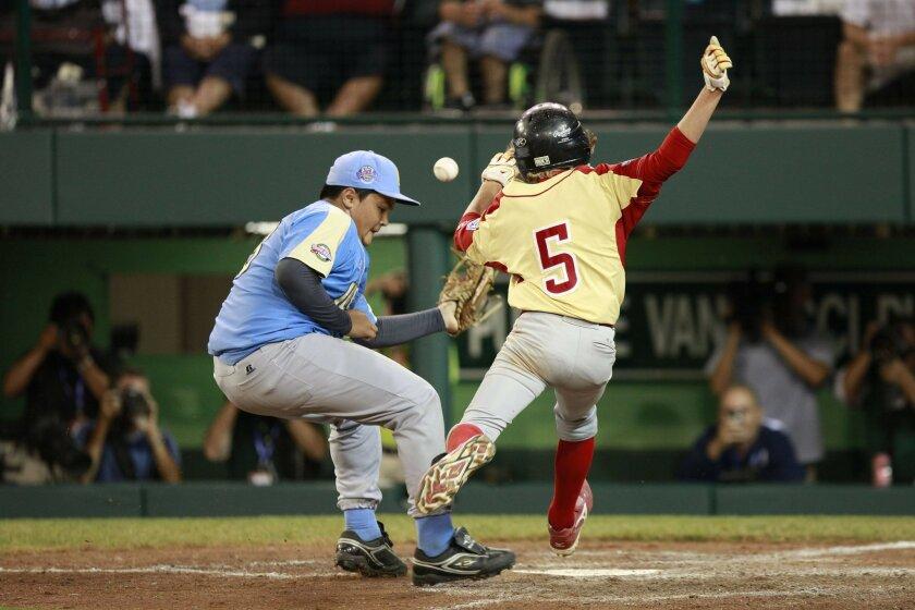 Park View pitcher Isaiah Armenta (left) collides with baserunner Jake Farrell in Warner Robins' nine-run fourth inning. (John R. McCutchen / Union-Tribune)