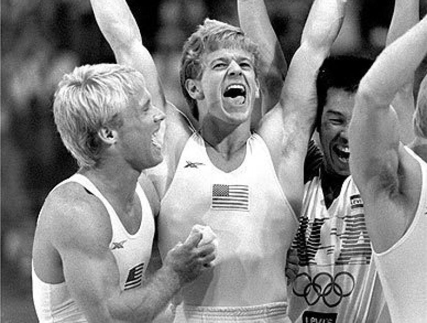Bart Conner, left, and Peter Vidmar, center, celebrate following the U.S. men's gymnastic team's gold medal.