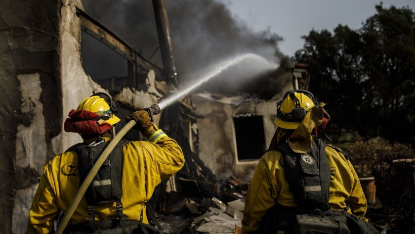Humboldt County firefighters hoses down smoldering flames inside a destroyed home after the Thomas Fire burned in Montecito, Calif. in December 2017.