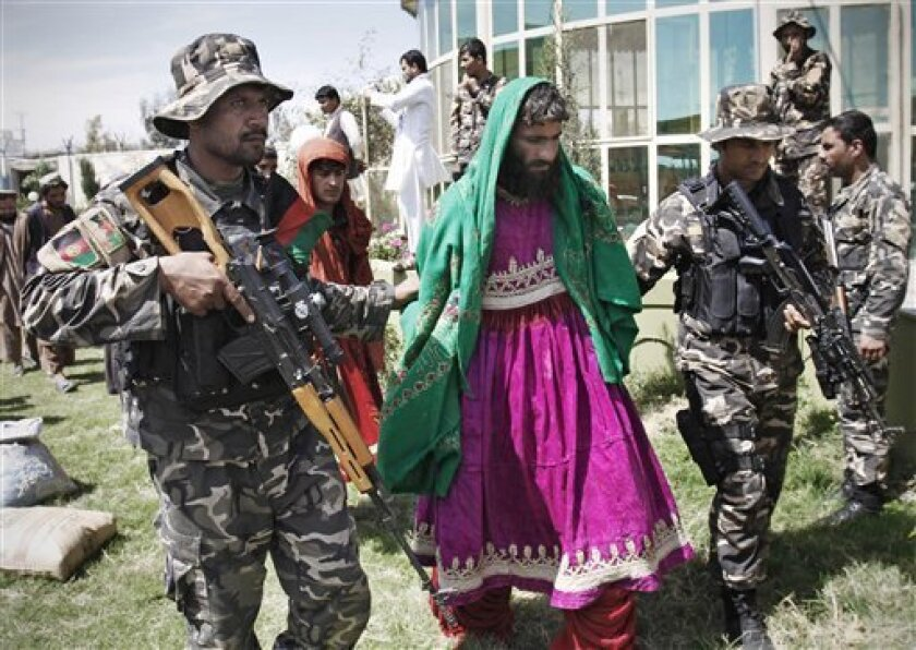 Afghan security forces escort Taliban militants clad in Afghan women dresses to be presented to the media at the Afghan intelligence department in Mehterlam, Laghman province, east of Kabul, Afghanistan, Wednesday, March 28, 2012.  Afghan Intelligence forces arrested seven Taliban militants today i
