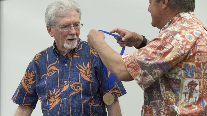 COSTA MESA, CA, May 19, 2016 -- Jim Carnett, left, receives a metal from friend Doug Bennett, the sc