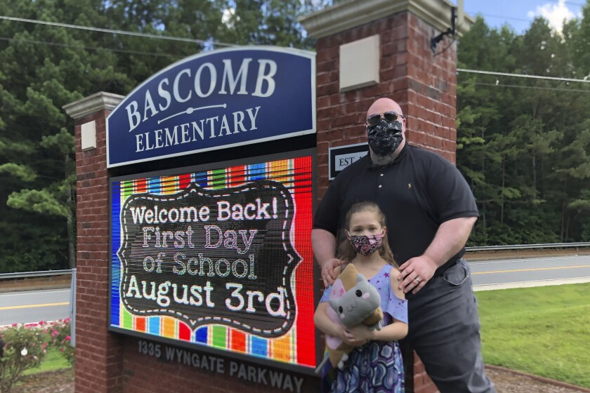 John Barrett and his daughter Autumn pose for photos outside Bascomb Elementary School in Woodstock, Ga., Thursday, July 23, 2020. Barrett says he will educate his daughter virtually and keep her out of in-person classes in Cherokee County schools, even though he's worried she will fall behind on her special education plans, because of concerns about COVID-19's spread. Cherokee County, near Atlanta, is one of many districts nationwide that gave parents a choice between in-person and all-online classes this fall. (AP Photo/Jeff Amy)
