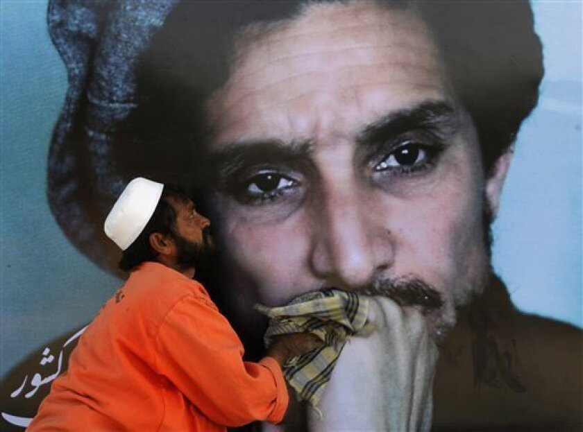 A worker cleans a poster of Afghanistan's Ahmad Shah Massoud, on the eve of his ninth death anniversary in Kabul, Afghanistan, Wednesday, Sept. 8, 2010. Two foreign suicide assassins, who had camouflaged themselves as journalists, killed Massoud on Sept. 9, 2001. (AP Photo/Andrew Biraj, Pool)