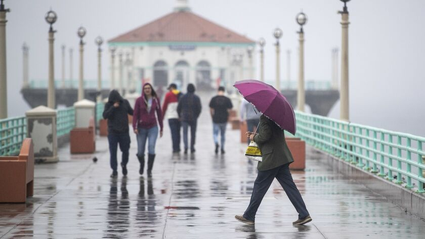 People use umbrellas and bundle up with rain jackets while walking down the pier amid light rain showers in Manhattan Beach on Feb. 28Thursday.
